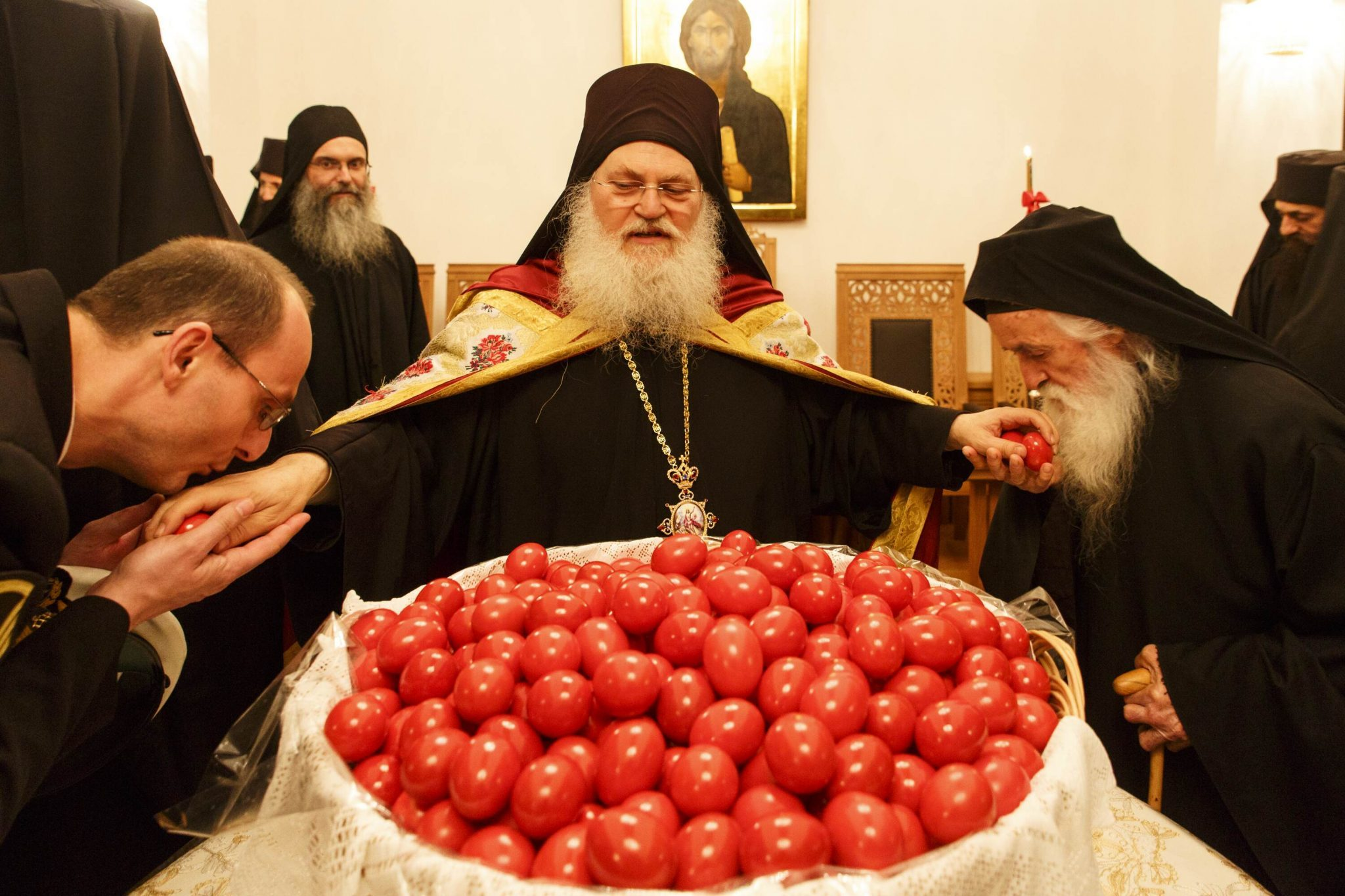 The Elder Ephraim is sharing red eggs after the service.